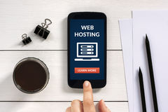 Web hosting concept on smart phone screen with office objects Stock Photo