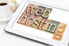 Web hosting concept. Text in letterpress wood type blocks on a digital tablet with a cup of coffee Stock Photo