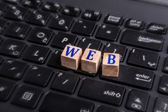 Web on laptop. Wooden block with web word graphic on laptop keyboard Royalty Free Stock Images