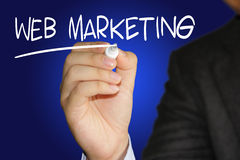Web Marketing. Business concept image of a businessman holding marker and write Web Marketing on blue background Stock Photo