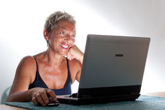 Web-mom-ster. A mature woman working at the laptop pc computer smiling Royalty Free Stock Photos