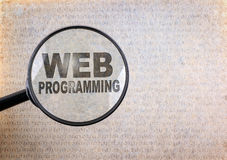 Web Programming. Magnifying optical glass on old paper backgroun Stock Images