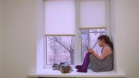 Web que juega adolescente de la muchacha en línea el animal doméstico del juego para el smartphone y perro que se sienta en alféi Fotos de archivo