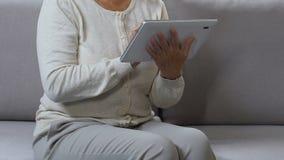 Web que practica surf de la mujer de mediana edad en la tableta, haciendo compras en línea, buscando descuento almacen de video