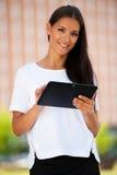 Web que practica surf joven hermoso de la mujer de negocios en una tableta i al aire libre Fotos de archivo libres de regalías