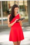 Web que practica surf joven hermoso de la mujer de negocios en una tableta i al aire libre Foto de archivo libre de regalías