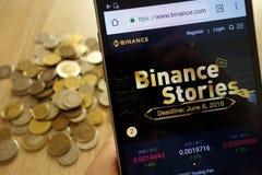 Web site da troca do cryptocurrency de Binance indicado no smartphone e na pilha de moedas fotografia de stock