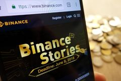 Web site da troca do cryptocurrency de Binance indicado no smartphone e na pilha de moedas imagem de stock