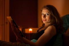 Web surfando da mulher bonita em uma tabuleta na cama antes de dormir fotos de stock royalty free