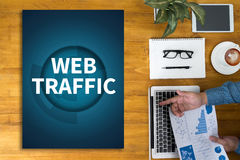 WEB TRAFFIC (business, technology, internet and networking concept ). Businessman working at office desk and using computer and objects, coffee, top view stock images