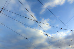 Web of tram cables with sky and clouds in background Royalty Free Stock Photos