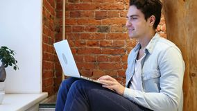 Web Video Chat on Laptop by Young Man, Sitting on Stairs. 4k , high quality stock footage