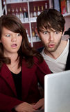 Web Weirdness. Woman and man staring in disbelief at a laptop Royalty Free Stock Photos