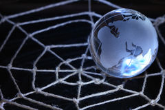 Web For World. Glass globe lying on web made from rope on dark background stock photo