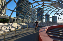 Webb Bridge - Melbourne. MELBOURNE,AUS - APR 14 2014:Cyclist cross on Webb Bridge.It's an award winning bridge forming a cycling and pedestrian link to the main Royalty Free Stock Photography