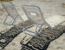 2 webbed beach chaise lounges with shadow pattern. 2 tubular beach chaise lounges with strong shadow web pattern in the sand stock photos