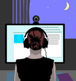 Webcam session. Woman in headphones in front of her computer communicating via web camera, the blue night sky with a crescent seen in the window Royalty Free Stock Photography