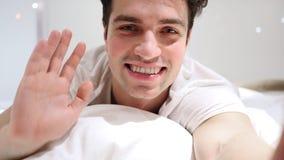 Webcamsikt för online-video pratstund av mannen som ligger i säng Royaltyfria Foton