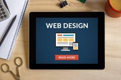 Webdesignkonzept auf Tablettenschirm mit Büro wendet ein Stockfotografie