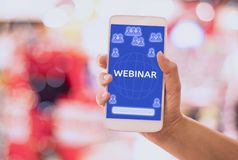 Webinar concept Woman hand hold Smart phone e-learning on mobile,with blue backgrounds, concept online and Skills Internet stock photography