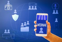 Webinar concept Woman hand hold Smart phone e-learning on mobile,with blue backgrounds, concept online and Skills Internet stock image