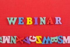 WEBINAR-ord på röd bakgrund som komponeras från träbokstäver för färgrikt abc-alfabetkvarter, kopieringsutrymme för annonstext Arkivbild