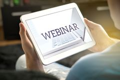 Webinar on tablet screen. Man holding smart mobile device and participating in a web seminar royalty free stock images