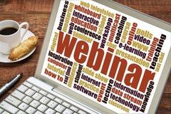 Webinar word cloud on laptop. Web seminar - webinar word cloud on a laptop screen with a cup of coffee Royalty Free Stock Photos