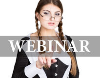 Webinar written on virtual screen. sexy secretary in a business suit with glasses, presses button on virtual screens Royalty Free Stock Photos