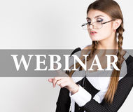 Webinar written on virtual screen. sexy secretary in a business suit with glasses, presses button on virtual screens Stock Photo