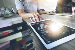 Website designer working digital tablet and computer laptop. With smart phone and digital design diagram and stack of books on wooden desk as concept Royalty Free Stock Image
