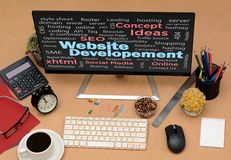 Website Development words collage on work station.  Stock Image