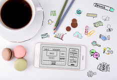 Website en mobiel app ontwikkelingsconcept Mobiele telefoon en koffiekop op een wit bureau royalty-vrije stock afbeeldingen