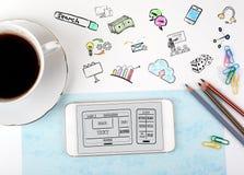 Website och mobilt app-utvecklingsbegrepp Mobiltelefon- och kaffekopp på ett vitt kontorsskrivbord Arkivbild
