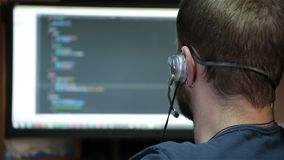 Male programmer working with code on screen stock footage