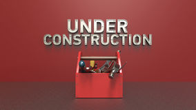 Website under construction concept with letters made out of metal and bolts,  toolbox full  tools in front  the wall Royalty Free Stock Photos