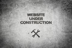 Website under construction. Text graphics website under construction with tool icons on grunge grey background stock photography