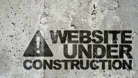 Website under construction !. Text 'website under construction !' in bold black uppercase letters on a gray concrete wall (surface) with texture stock photography
