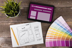 Website wireframe sketch and digital tablet on wooden table Royalty Free Stock Photography