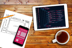 Website wireframe sketch and programming code on digital tablet. Website wireframe sketch, mobile phone and programming code on digital tablet stock image