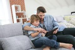 Websurfingf del padre y del hijo en una tableta en casa Imágenes de archivo libres de regalías