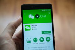 WeChat application in google play store. Los Angeles, november 2, 2017: Man hand holding smartphone with WeChat application in google play store Stock Image