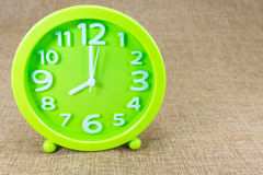 Wecker auf brauner Sackleinenhintergrundshow acht O ` Uhr oder 8:00 a M Lizenzfreie Stockfotos