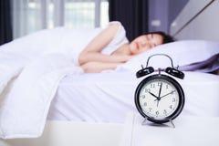 Wecker auf der Tabelle und Frau, die auf Bett im Schlafzimmer schlafen Lizenzfreie Stockfotografie