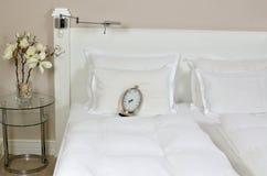Wecker auf einem Bett Stockbild