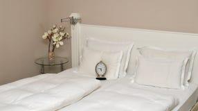 Wecker auf einem Bett im Schlafzimmer Stockfotografie