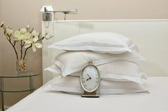 Wecker auf einem Bett mit Kissen Lizenzfreies Stockfoto