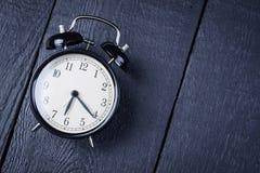 Wecker auf einer schwarzen Holzoberfläche Stockfotos