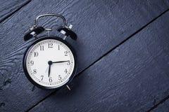 Wecker auf einer schwarzen Holzoberfläche Stockbilder