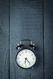 Wecker auf einer schwarzen Holzoberfläche Lizenzfreies Stockfoto